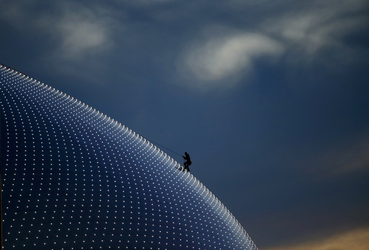 A person climbs on the Bolshoi Dome, one of the ice hockey venues, before the medals ceremony during the 2014 Sochi Winter Olympics February 14, 2014. REUTERS/Marko Djurica