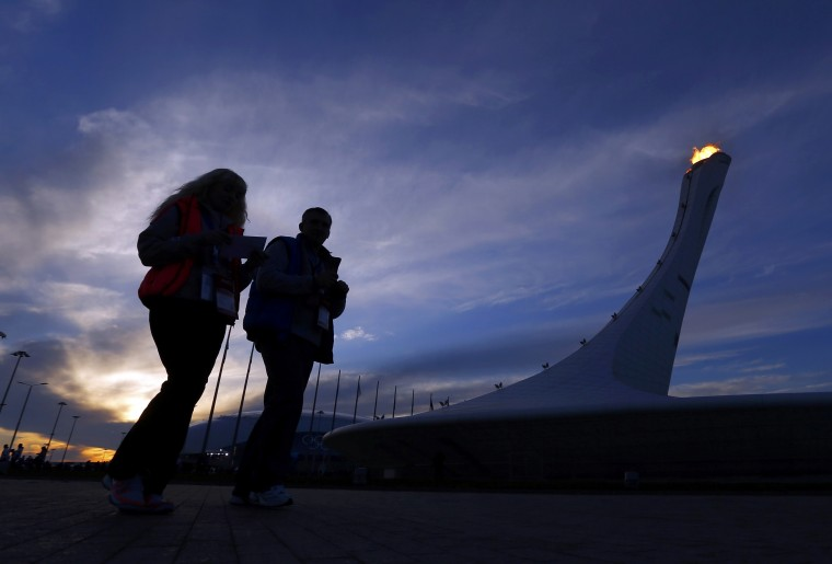 People walk past the Olympic cauldron as the sun sets on the Olympic Park at the 2014 Sochi Winter Olympics, February 14, 2014. REUTERS/Laszlo Balogh