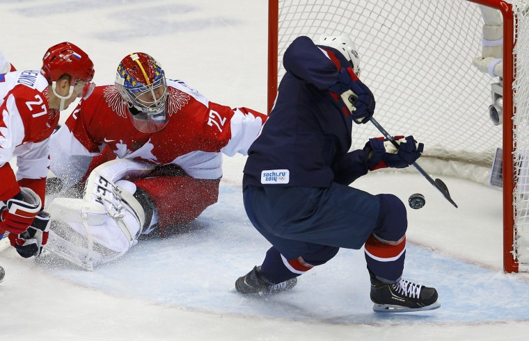 Team USA's Cam Fowler (R) scores on Russia's goalie Sergei Bobrovski and Russia's Alexei Tereshenko (L) during the second period of their men's preliminary round ice hockey game at the 2014 Sochi Winter Olympics, February 15, 2014. REUTERS/Brian Snyder