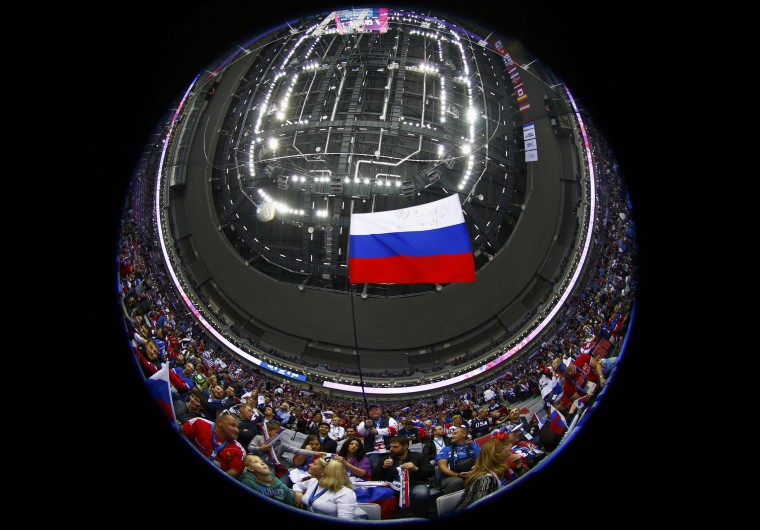 A Russian flag is seen before the men's preliminary round hockey game between Russia and USA at the Sochi 2014 Winter Olympic Games February 15, 2014. Picture taken with a fisheye lens. REUTERS/Mark Blinch