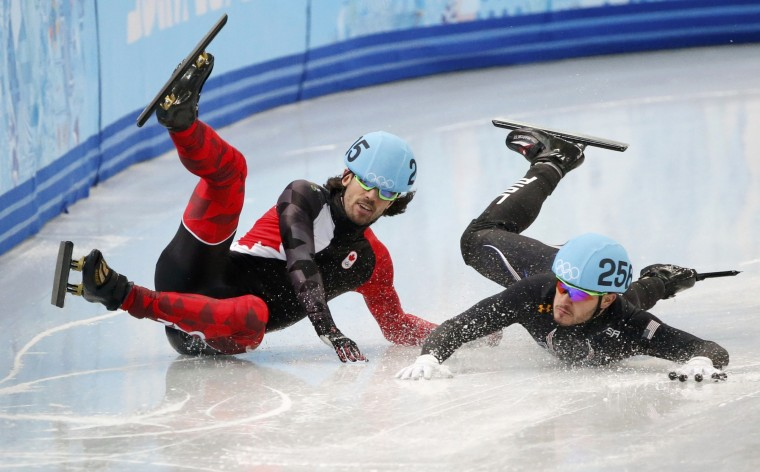 Canada's Charles Hamelin (L) and Eduardo Alvarez of the U.S. fall during the men's 1,000 metres short track speed skating quarter-finals race at the Iceberg Skating Palace at the Sochi 2014 Winter Olympic Games February 15, 2014. REUTERS/Lucy Nicholson