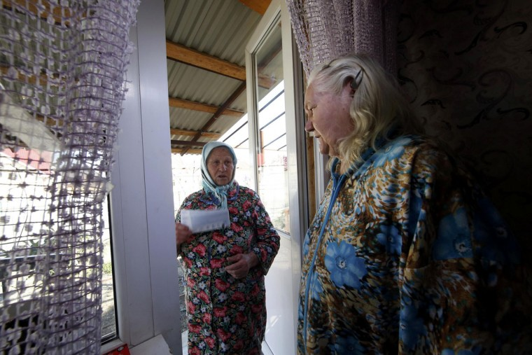 A neighbour brings Lyudmila Frolova (R) tickets to an Olympic hockey game provided by the government to relocated residents in Sochi, February 12, 2014. (Eric Gaillard/REUTERS)