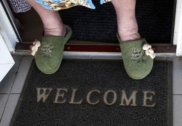 Lyudmila Frolova stands on a welcome mat in front of her home in Sochi, February 12, 2014. (Eric Gaillard/REUTERS)