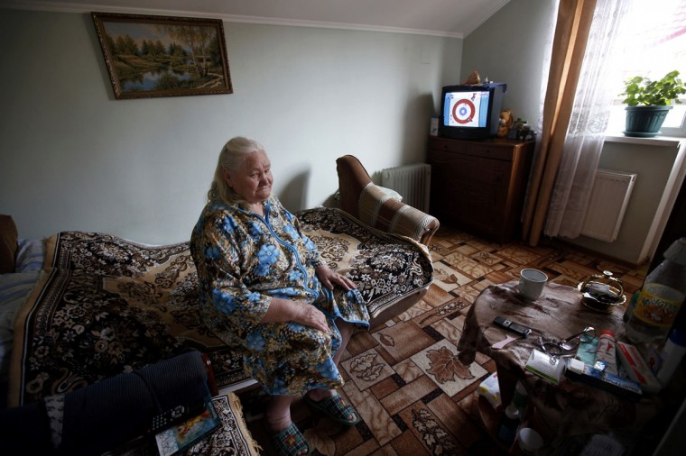 Lyudmila Frolova watches Olympic curling on television in Sochi, February 11, 2014. (Eric Gaillard/REUTERS)
