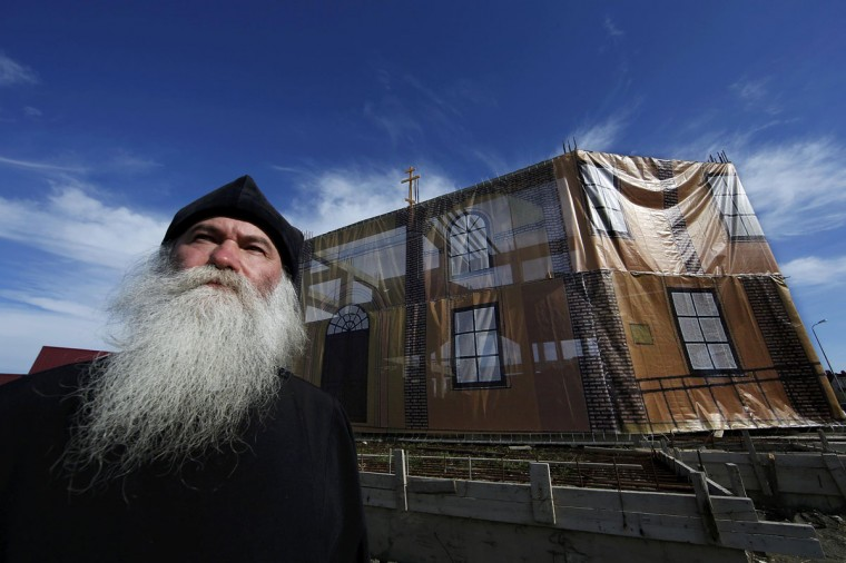 """Archpriest Georgy Efimov poses in front of the tarp-covered frame of a new church his community is building in Sochi, February 12, 2014. His community of """"Old Believers"""", who follow Russian Orthodox traditions dating from before reforms in the 17th century, lost their church to make way for the construction of the Olympic site. Efimov said getting building materials into the area had been nearly impossible while the Olympic construction wore on. (Eric Gaillard/REUTERS)"""