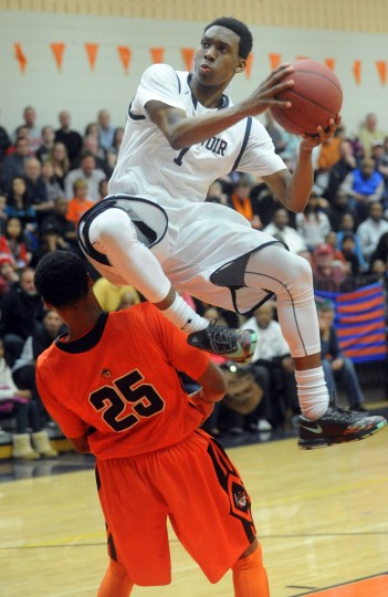 Reservoir's Aaron McDonald jumps over City's Juwan Grant on his way to the hoop during the 3A East regional championship boys basketball game at Reservoir High School on Friday, March 7. (Brian Krista/BSMG)