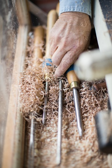 Chesapeake Woodturners member Lou Rudinski, of Millersville, grabs a tool surrounded by wood shavings that is used to shape wood on a lathe. (Nate Pesce/BSMG Photo)