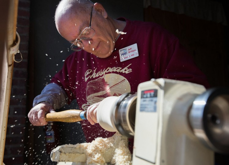 Chesapeake Woodturners member Jeff Bridges, of Laurel, uses a tool to shave down the wood as debris and pieces fly out from the machine. (Nate Pesce/BSMG Photo)