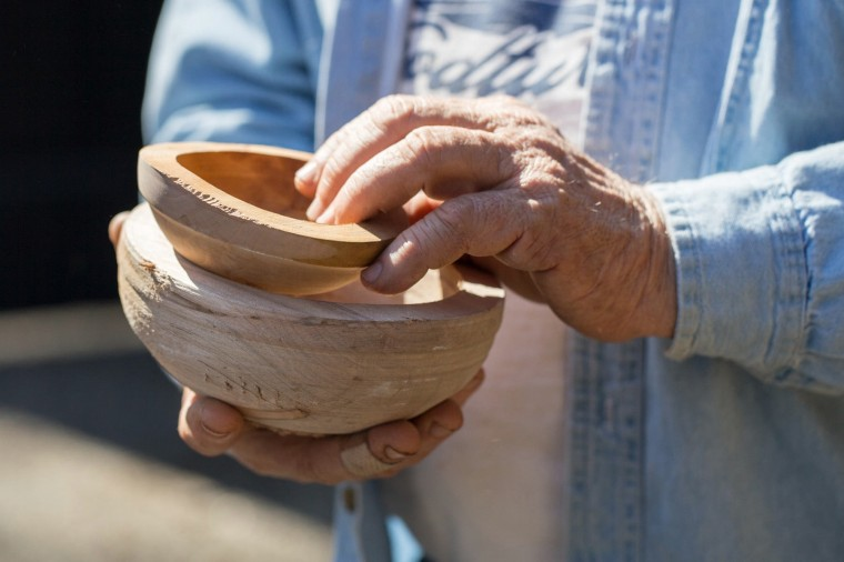 Chesapeake Woodturners member Lou Rudinski, of Millersville, shows visitors some unfinished bowls at the woodturners demonstration. (Nate Pesce/BSMG Photo)