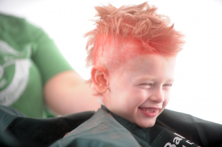 Ethan Sampson of Havre de Grace smiles as he's seen with a red mohawk while in the process of having his head shaved during the St. Baldrick's Foundation head-shaving fundraiser at Bill Bateman's Bistro in Havre de Grace on Saturday, March 15. The St. Baldrick's Foundation is a volunteer-driven charity that funds grants for childhood cancer research. (Brian Krista/BSMG)