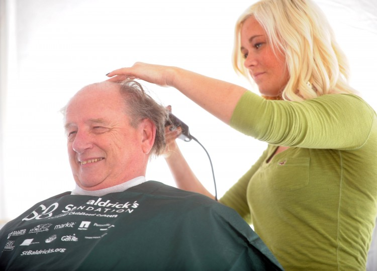 Charlie Packard, president of the Susquehanna Hose Company, has clippers taken to his hair by Color Images Salon stylist Amanda Scott during the St. Baldrick's Foundation head-shaving fundraiser at Bill Bateman's Bistro in Havre de Grace on Saturday, March 15. (Brian Krista/BSMG)