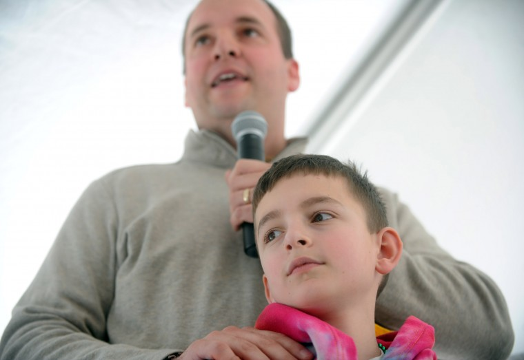 Nick Saacks of Havre de Grace stands with his ten-year old son Thomas, who's currently in remission from liver cancer, as he thanks the crowd for their support during the St. Baldrick's Foundation head-shaving fundraiser at Bill Bateman's Bistro in Havre de Grace on Saturday, March 15. (Brian Krista/BSMG)