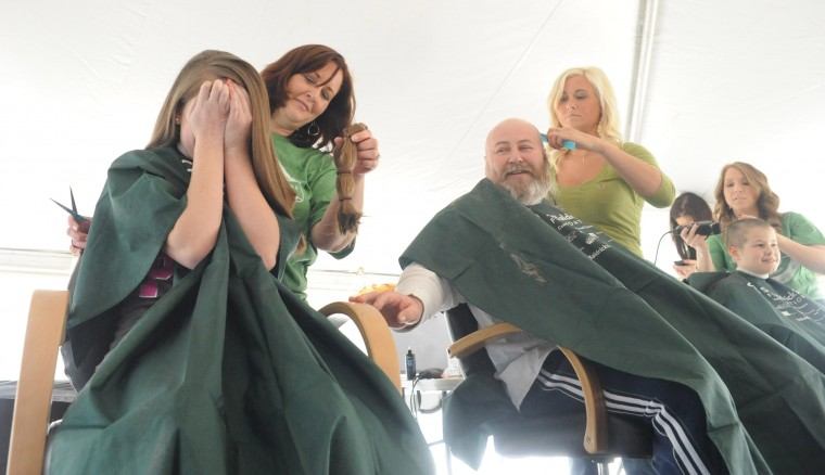 Kendell Hurst, 13, of Havre de Grace shields her eyes as stylist Jennifer Old of Havre de Grace tries to show her the hair she had cut off to donated to Wigs for Kids during the St. Baldrick's Foundation head-shaving fundraiser at Bill Bateman's Bistro in Havre de Grace on Saturday, March 15. (Brian Krista/BSMG)