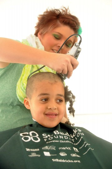 Shane Cardwell, 6, of Havre de Grace half-heartedly smiles as his hair is shaved off by Color Images Salon stylist Brittney Pasley during the St. Baldrick's Foundation fundraiser at Bill Bateman's Bistro in Havre de Grace on Saturday, March 15. The St. Baldrick's Foundation is a volunteer-driven charity that funds grants for childhood cancer research. (Brian Krista/BSMG)