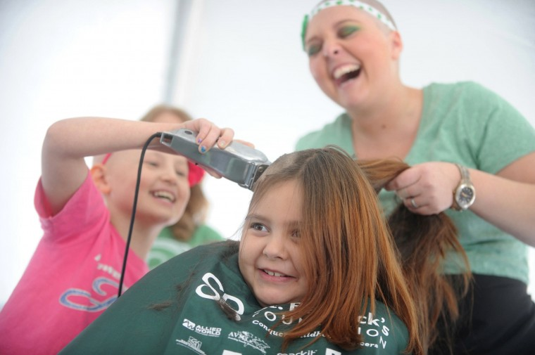 Kelsi Muller of Delta, Pa. reacts as her best friend Serena Whitt of Delta, Pa., left, a fellow third grader at Delta-Peach Bottom Elementary, joyfully take clippers to her hair under the guidance of Color Images Salon stylist Brittney Pasley, who also had her hair shaved during the St. Baldrick's Foundation fundraiser, at Bill Bateman's Bistro in Havre de Grace on Saturday, March 15. (Brian Krista/BSMG)