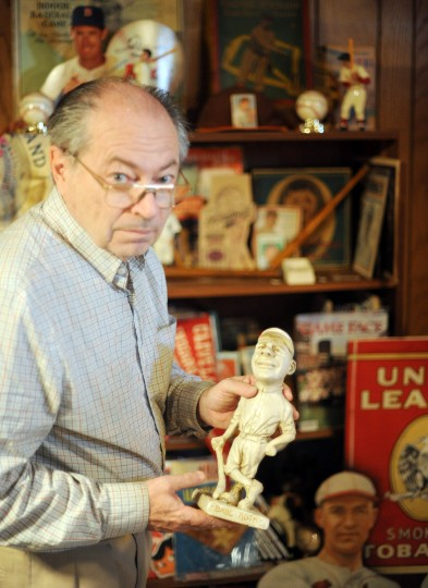 Ted Patterson, baseball memorabilia collector, shows off a rare figurine of Babe Ruth from his early baseball years as a member of the Boston Red Sox, at his home in Towson on Friday, March 21. (Brian Krista/BSMG)