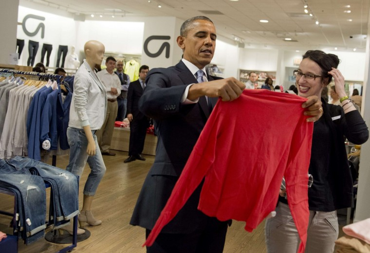 President Barack Obama looks at a shirt as he shops for clothing for his family with Gap employee Susan Panariello at a New York City store to highlight his proposal to raise the federal minimum wage. (Saul Loeb/AFP/Getty Images)