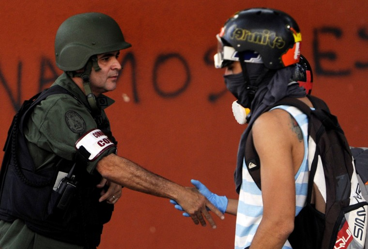 """A Venezuelan National Guard officer shakes hands with an anti-government activist during a protest in Caracas against the Venezuelan government of President Nicolas Maduro. The death toll from five weeks of political unrest in Venezuela has climbed to 21 after a student was fatally shot in the city of San Cristobal, authorities said. Maduro invited opposition leaders and students for a """"peace talks"""" meeting on March 12. (Leo Ramirez/AFP/Getty Images)"""