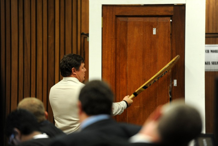 Police forensic expert Col. Johannes Vermeulen hits the door with a cricket bat as he re-enacts how South African Paralympian Oscar Pistorius broke down the door of the bathroom where he shot and killed his girlfriend during the trial's cross-examination at the North Gauteng High Court in Pretoria, South Africa. Pistorius's murder trial was set to hear more details on the autopsy of his slain girlfriend Reeva Steenkamp, a day after the star sprinter threw up as he listened to a graphic account of the gunshot injuries he inflicted on his lover. (Wener Beukes/AFP/Getty Images pool photo)