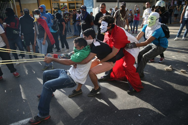 Protesters sling stones at Venezuelan national guard troops during an anti-government demonstration in Caracas, Venezuela. Wednesday marks the first anniversary of Hugo Chavez' death. For three weeks protesters have blocked roads throughout the country and clashed with security forces of the government of Chavez' chosen successor President Nicolas Maduro. (John Moore/Getty Images)