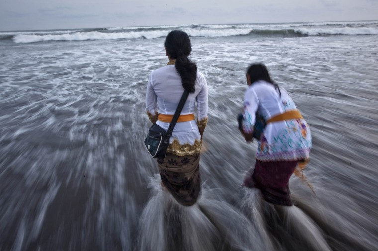 Hindu devotees wash their faces with sea water as they pray during the Melasti ritual ceremony at Parangkusumo beach on March 29, 2014 in Yogyakarta, Indonesia. (Photo by Ulet Ifansasti / Getty Images)