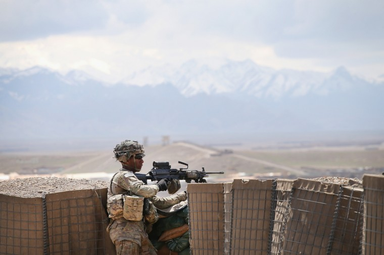 PFC Jeremy Ortiz from Ontario, California with the U.S. Army's 2nd Battalion 87th Infantry Regiment, 3rd Brigade Combat Team, 10th Mountain Division keeps watch from inside an Afghan National Army (ANA) outpost during a patrol outside of Forward Operating Base (FOB) Shank on March 29, 2014 near Pul-e Alam, Afghanistan. (Scott Olson / Getty Images)
