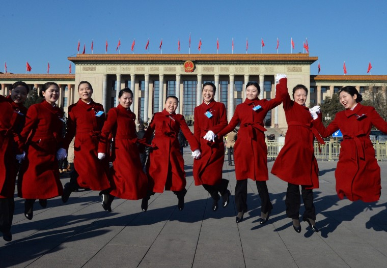 Chinese hostesses jump for photographers before the start of the National People's Congress (NPC) at the Great Hall of the People (back) in Beijing. China's annual show of political theater, the NPC is the first under the new Communist Party leadership and is facing intractable problems including endemic corruption, slowing economic growth and tensions with neighboring countries. (Mark Ralston/Getty Images)