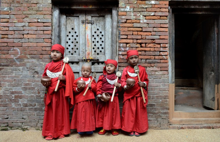 A group of Nepalese Buddhist boys pose as they attend Bratabandha, a coming-of-age ceremony in Kathmandu. In Newari culture of the Shakya caste, the heads of young boys are shaved and they wear a dress of a monk during the Bratabandha ceremony, which combines chudakarma and upanayana, among the hill communities of Nepal. (Prakash Mathema/Getty Images)