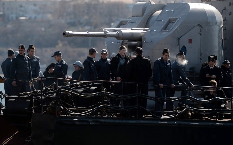 Ukrainian soldiers stand guard on board the navy corvette Ternopil as Russian forces patrol nearby in the harbor of the Ukrainian city of Sevastopol. The Ukrainian soldiers hung matresses on the edge of the navy ship's railing to prevent Russian forces from forcefully boarding the ship with grappling hooks. Russian forces seized partial control of two Ukrainian missile bases in Crimea today as Western and Russian leaders stepped up efforts to defuse the region's worst crisis since the Cold War. (Filippo Monteforte/Getty Images)