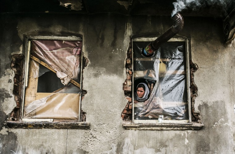 A Syrian refugee woman looks out from a window with no glass, in a house in the Kucukpazar area of Istanbul. Syrian government forces are waging a campaign of siege warfare and starvation against civilians as part of its military strategy, a UN-mandated probe said on March 5. Syria's war has since March 2011 killed more than 140,000 people and forced millions more to flee. (Gurcan Ozturk/Getty Images)