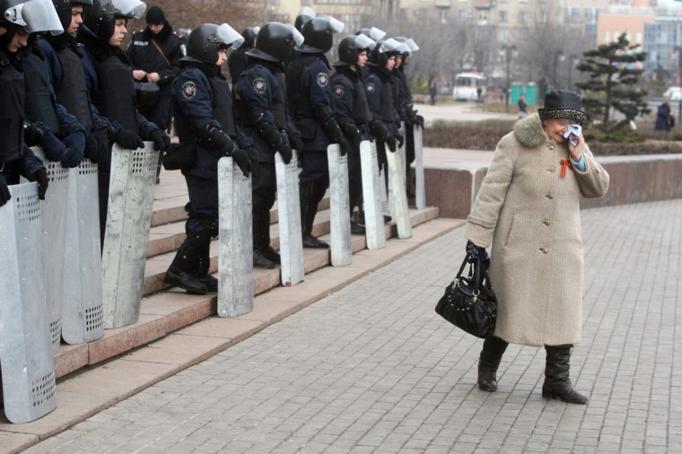 "An elderly pro-Russian activist cries as Urkainian riot police officers stand guard in front of the regional state administration building in the eastern Ukrainian city of Donetsk. The Pro-Russian self-proclaimed governor of the region Paul Gubarev called on ""thousands"" of pro-Russian supporters to be ready to storm the building again. Meanwhile Russian forces seized partial control of two Ukrainian missile bases in Crimea today as Western and Russian leaders stepped up efforts to defuse the region's worst crisis since the Cold War. (Alexander Khudoteply/Getty Images)"