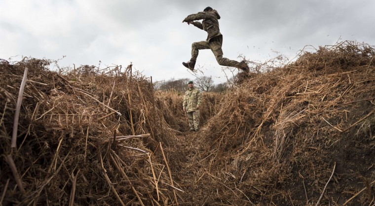Rifleman Stuart Gray leaps across an overgrown 'trench' in a practice WW1 battlefield in Gosport, in southern England, on March 6, 2014. Remains of an entire practice battlefield, with two sets of opposing trench systems and a No Mans Land between, used for training troops before they were sent to the Front in the First World War, has been discovered on Ministry of Defence heathland in Gosport, Hampshire. CREDIT: CHRIS ISONCHRIS ISON/ - AFP/GETTY IMAGES