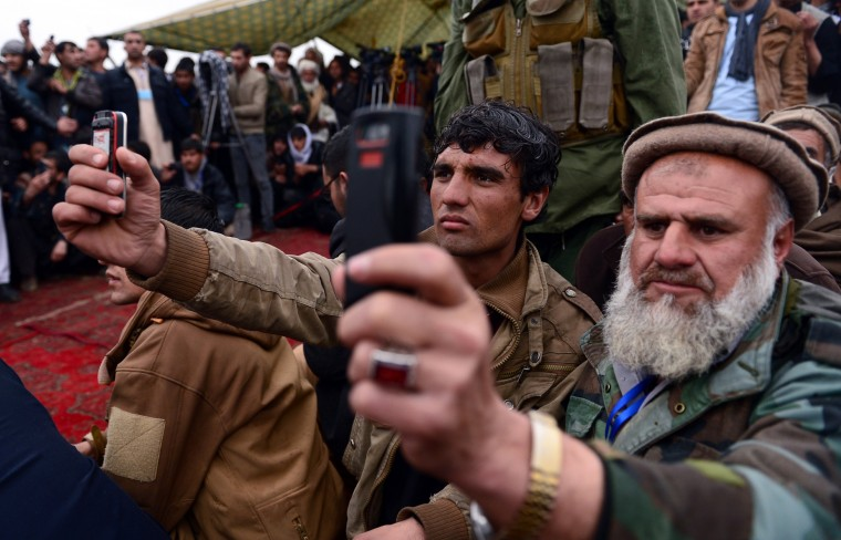 Supporters of Afghan presidential candidate and former Mujahideen leader and hardline Islamist Abdul Rasul Sayyaf record footage on their mobile phones during an election rally in Shakardara district of Kabul province on March 14. Afghanistan's April 5 election is the third presidential poll since the fall of the Taliban with 11 candidates contesting the polls. (Wakil Kohsar/AFP/Getty Images)