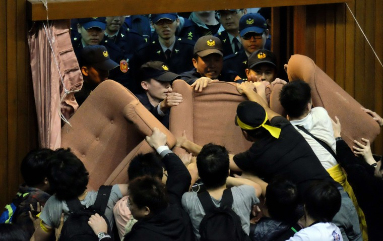 Police officers try to enter the Taiwanese Parliament which is occupied by activists to protest against moves by the ruling Kuomintang party to ratify a contentious trade agreement with China, in Taipei. Late on March 18 around 200 students and activists broke through a security barrier and took over the main chamber in Taiwan's parliament, singing and dancing in protest against the trade agreement. (Sam Yeh/Getty Images)