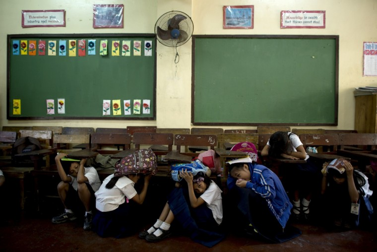 Students of Bagong Silangan Elementary school cover their head during an earthquake drill in Manila. The students participated in a national emergency earthquake drill that aims to generate awareness on disaster risk reduction and assess their capacity level to respond during a disaster. (Noel Celis/Getty Images)
