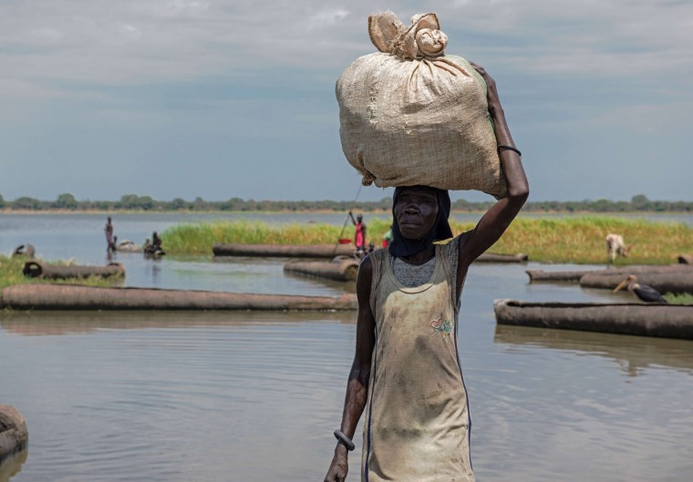 A woman carries produce from her farm across a river in Yirol. Over 10,000 people have died and nearly a million have been displaced after violence broke out in South Sudan in December 2014. An additional 190,000 people have also reportedly fled the country to neighboring Uganda, Ethiopia, Kenya and Sudan. (Charles Lomodong/Getty Images)