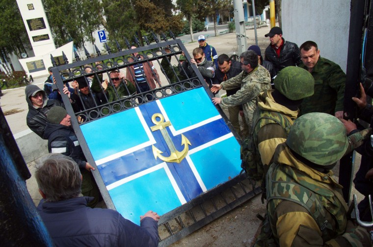 Pro-Russian protesters remove the gate of Ukrainian navy headquarters as Russian troops stand guard in Crimean city of Sevastopol. Pro-Russian protesters seized Ukraine's Crimean naval headquarters and captured its commander on Wednesday after Moscow claimed the peninsula and the first casualties ratcheted up stakes in the worst East-West standoff since the Cold War. (Vasiliy Batanov/Getty Images)