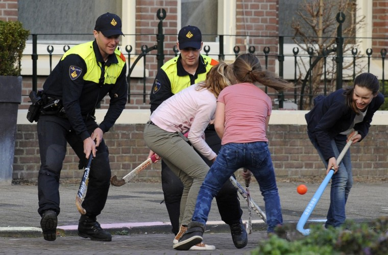 Dutch policemen play field hockey with girls in a street in The Hague. (John Thys/Getty Images)