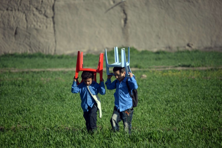 Afghan school children carry plastic chairs on their heads as they walk to school in the morning in Mazar-i-Sharif. The literacy rate in Afghanistan is about 30 percent and about 42 percent of the country's population is under the age of 14. According to UNICEF more boys than girls attend classes in primary school in Afghanistan. (Farshad Usyan/Getty Images)