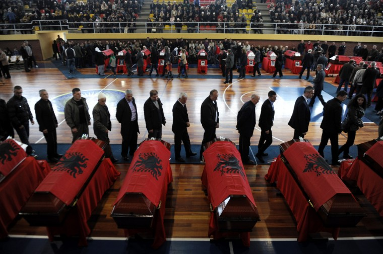 Kosovo Albanians pay homage over the coffins containing mortal remains during a funeral ceremony in the town Suva Reka for the 27 Kosovo Albanians killed by Serbian security forces during the 1998-1999 Kosovo war. (Armend Nimani/Getty Images)