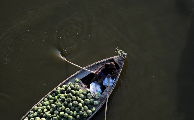 An Indian laborer transports pumpkins on a boat at Fafamau village near Allahabad. (Sanjay Kanojia/Getty Images)