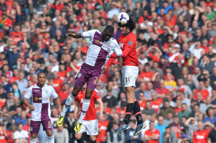 Manchester United's Belgian midfielder Marouane Fellaini (R) wins a header against Aston Villa's Zaire-born Belgian striker Christian Benteke (L) during the English Premier League football match between Manchester United and Aston Villa at Old Trafford in Manchester, northwest England, on March 29, 2014. (Andrew Yates / AFP/Getty Images)