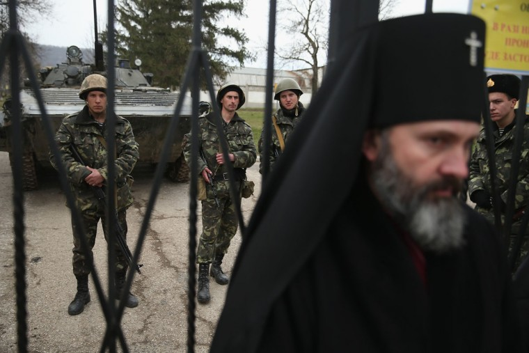 An Orthodox clergyman stands to bar entrance at the gate outside a Ukrainian military base that was surrounded by several hundred Russian-speaking soldiers as Ukrainian soldiers and a Ukrainian army tank stand just inside the gate in Crimea on March 2, 2014 in Perevanie, Ukraine. Several hundred heavily-armed soldiers not displaying any identifying insignia took up positions outside the base and parked several dozen vehicles, mostly trucks and patrol cars, nearby. The new government of Ukraine has appealed to the United Nations Security Council for help against growing Russian intervention in Crimea, where thousands of Russian troops reportedly arrived in recent days at Russian military bases there and also occupy key government and other installations. World leaders are scrambling to persuade Russian President Vladimir Putin to refrain from further escalation in Ukraine. Ukraine has put its armed forces on combat alert. (Sean Gallup/Getty Images)