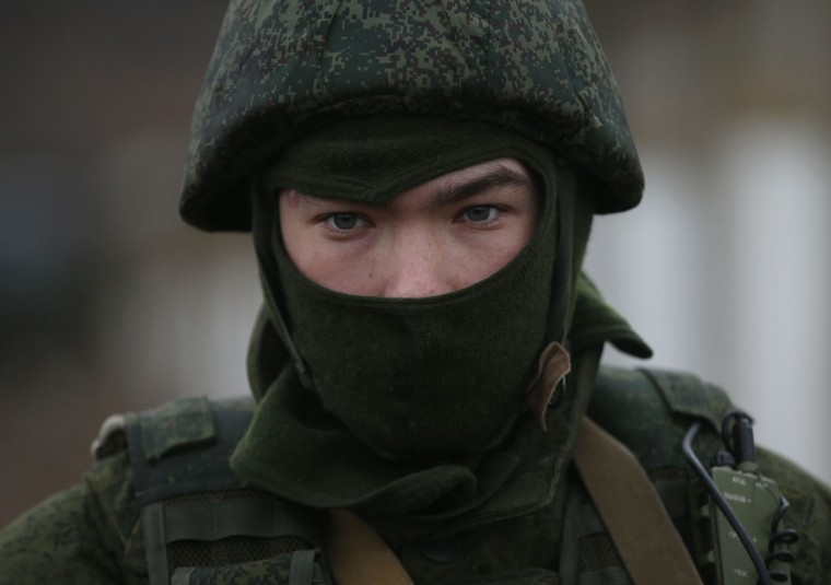 A soldier who was among several hundred that took up positions around a Ukrainian military base stands near the base's periphery in Crimea on March 2, 2014 in Perevanie, Ukraine. Several hundred heavily-armed soldiers not displaying any identifying insignia took up positions outside the base and parked several dozen vehicles, mostly trucks and patrol cars, nearby. (Sean Gallup/Getty Images)