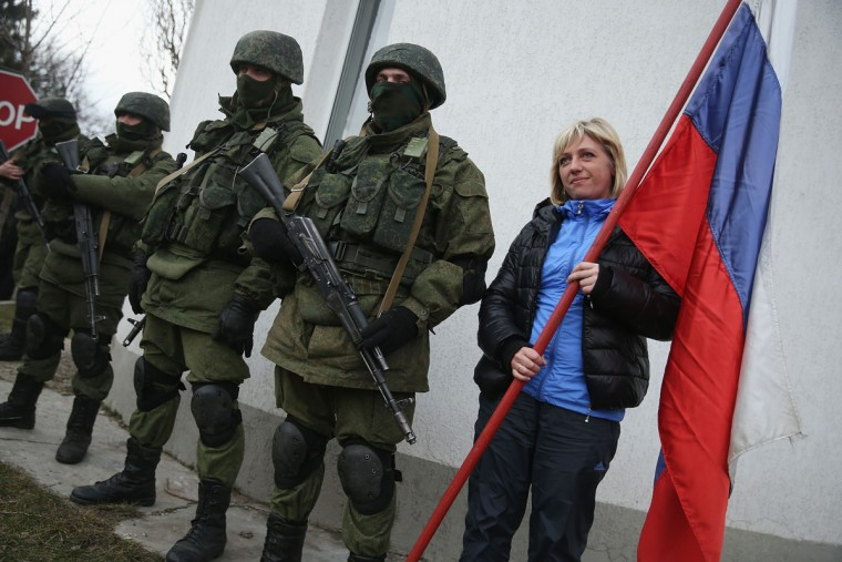 A pro-Russian young woman clutches a Russian flag as she poses for snapshots with soldiers who had taken up positions around a Ukrainian military base in Crimea on March 2, 2014 in Perevanie, Ukraine. (Sean Gallup/Getty Images)