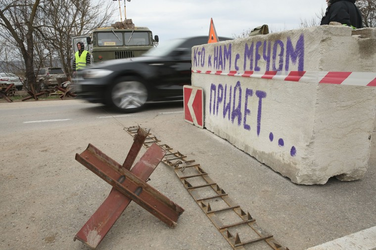 "A car passes through a checkpoint manned by pro-Russian militants on a road leading to Sevastopol next to a concrete block with writing that reads: ""He who approaches us with a sword . . . "" in Crimea on March 2, 2014 near Verkhn'osadove, Ukraine. (Sean Gallup/Getty Images)"