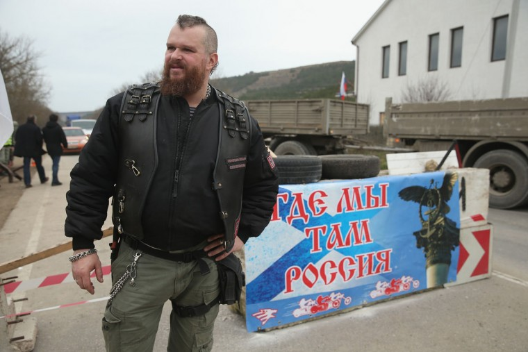 "A pro-Russian militant who identifed himself as Nazar and says he is a member of the ""Night Wolves"" biker club helps man a checkpoint next to a sign that reads: ""Where we are, there is Russia"" on a road leading to Sevastopol in Crimea on March 2, 2014 near Verkhn'osadove, Ukraine. (Sean Gallup/Getty Images)"