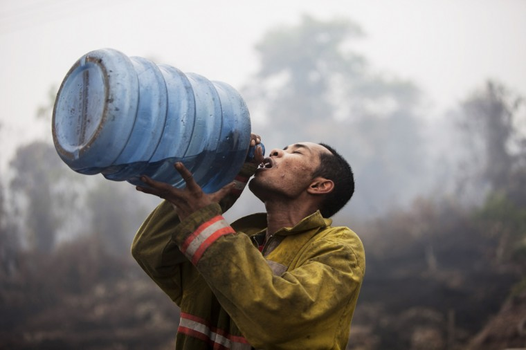A firefighter takes a drink after extinguishing a fire burning at a plantation on March 3, 2014 in Siak, Riau, Indonesia. The air quality reached dangerous levels while forest fires continue to burn in Indonesia's Riau province after a long period of dry weather. The smokey haze has reportedly caused more than 25,000 to have respiratory problems. (Oscar Siagian/Getty Images)