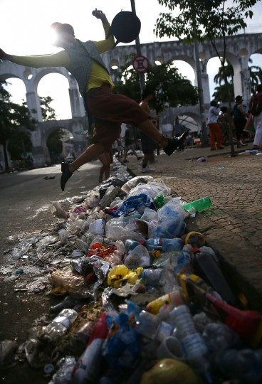 A reveler jumps over trash while posing during a street carnival bloco in the Lapa neighborhood on March 5, 2014 in Rio de Janeiro, Brazil. (Photo by Mario Tama/Getty Images)