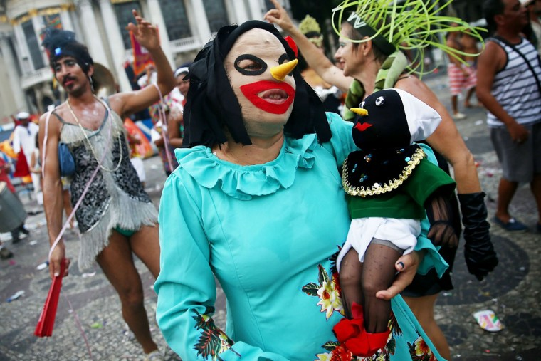 A reveler carries a doll during a street carnival bloco while marching in the Centro neighborhood on March 5, 2014 in Rio de Janeiro, Brazil. (Photo by Mario Tama/Getty Images)